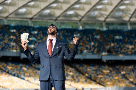 Photo pour Jeune homme d'affaires en costume et lunettes avec de l'argent montrant yeas geste et crier au stade - image libre de droit