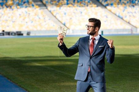 Photo pour Jeune homme d'affaires souriant en costume et lunettes avec de l'argent montrant geste oui au stade - image libre de droit