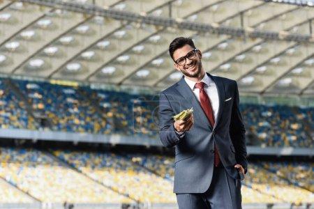 Photo pour Un jeune homme d'affaires souriant en costume et lunettes donnant de l'argent au stade - image libre de droit