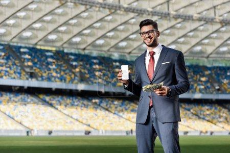 Photo pour Jeune homme d'affaires souriant en costume et lunettes avec de l'argent montrant smartphone avec écran blanc au stade - image libre de droit
