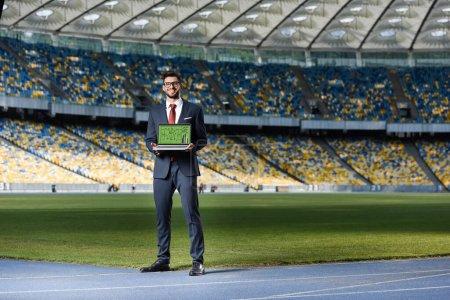 Photo pour Jeune homme d'affaires souriant en costume montrant ordinateur portable avec formation de football à l'écran au stade - image libre de droit