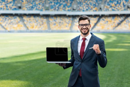 Photo for Smiling young businessman in suit showing yes gesture while holding laptop with blank screen at stadium - Royalty Free Image