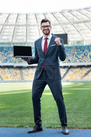 Photo for Smiling young businessman in suit showing yeah gesture while holding laptop with blank screen at stadium - Royalty Free Image