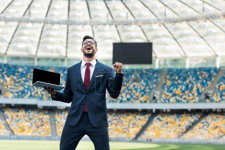 Photo pour Vue à faible angle d'un jeune homme d'affaires heureux en costume montrant un geste positif et tenant un ordinateur portable avec écran vierge au stade - image libre de droit