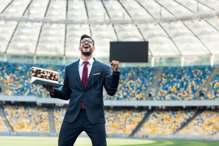 Photo pour KIEV, UKRAINE - 20 JUIN 2019 : low angle view of happy young business man in suit showing yes gesture and holding laptop with depositphotos website at stadium - image libre de droit