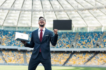 Photo for KYIV, UKRAINE - JUNE 20, 2019: low angle view of happy young businessman in suit showing yes gesture and holding laptop with google website at stadium - Royalty Free Image