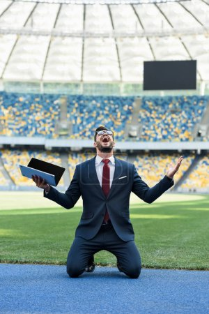 Photo for Happy young businessman in suit holding laptop with blank screen while standing on knees at stadium - Royalty Free Image
