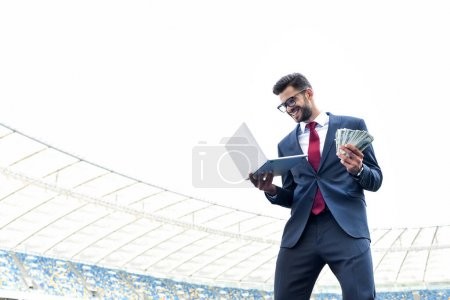 Photo for Low angle view of happy young businessman in suit holding laptop and money at stadium, sports betting concept - Royalty Free Image