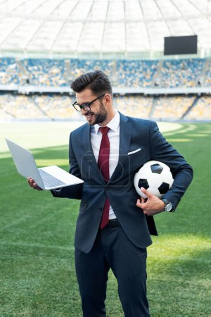 Photo for Smiling young businessman in suit with laptop and soccer ball at stadium, sports betting concept - Royalty Free Image