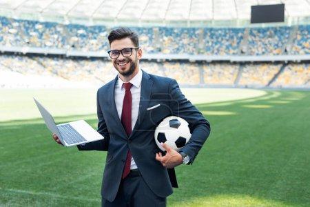 Photo pour Jeune homme d'affaires souriant en costume avec ordinateur portable et ballon de football assis sur le terrain de football au stade, concept de paris sportifs - image libre de droit