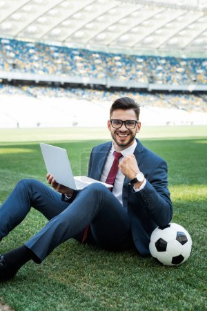 Photo for Smiling young businessman in suit with laptop and soccer ball sitting on football pitch and showing yes gesture at stadium, sports betting concept - Royalty Free Image