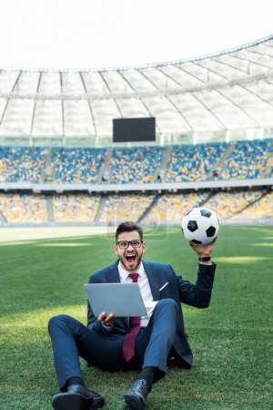 Photo for Happy young businessman in suit with laptop and soccer ball sitting on football pitch at stadium, sports betting concept - Royalty Free Image