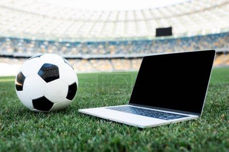 Photo pour Ballon de football et ordinateur portable avec écran vierge sur terrain de football herbeux au stade - image libre de droit