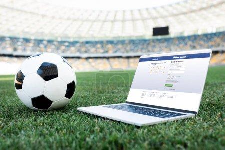 Photo pour KYIV, UKRAINE - 20 JUIN 2019 : ballon de football et ordinateur portable avec site facebook sur terrain de football herbeux au stade - image libre de droit