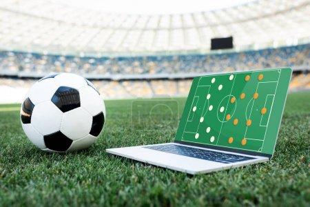 футбольный мяч и ноутбук с образованием на экране на травяном футбольном поле на стадионе