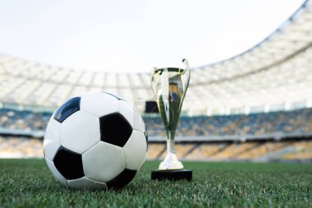 Photo for Soccer ball and trophy on grassy football pitch at stadium - Royalty Free Image
