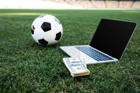 Photo pour Foyer sélectif du ballon de football, de l'argent et de l'ordinateur portable avec écran vierge sur le terrain de football herbeux au stade, concept de pari en ligne - image libre de droit