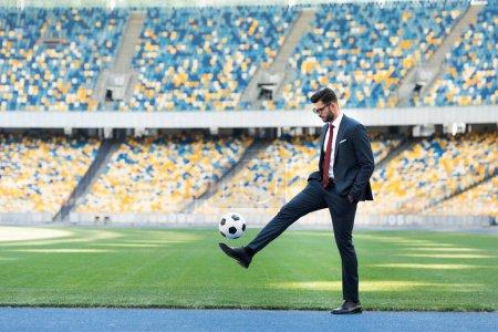 Photo pour Jeune homme d'affaires en costume et lunettes jouant au ballon de soccer au stade - image libre de droit