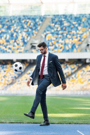 Photo pour Jeune homme d'affaires en costume et lunettes jouant avec le ballon de football au stade - image libre de droit