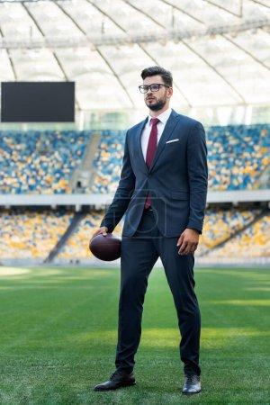 Photo pour Jeune homme d'affaires en costume et lunettes avec ballon de rugby au stade - image libre de droit
