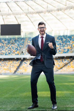 happy young businessman in suit and glasses with rugby ball showing yes gesture at stadium