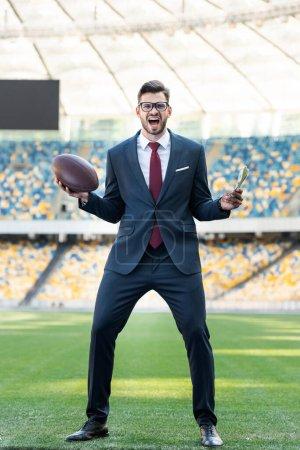 Photo pour Jeune homme d'affaires en costume et lunettes avec balle de rugby criant au stade - image libre de droit