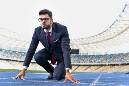 Photo pour Jeune homme d'affaires en costume en position de départ sur piste de course au stade - image libre de droit