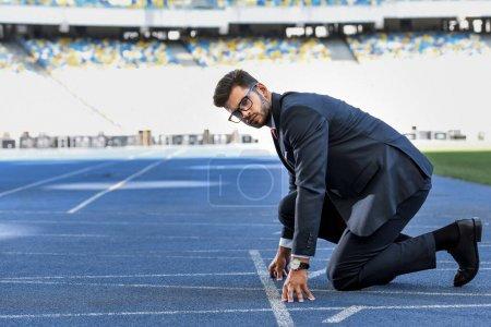 Photo pour Vue de côté du jeune homme d'affaires en costume en position de départ sur la piste de course au stade - image libre de droit
