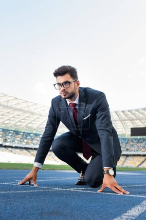 Photo for Young businessman in suit in start position on running track at stadium - Royalty Free Image