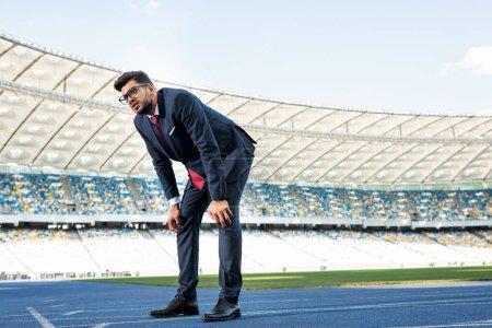Photo pour Jeune homme d'affaires en costume sur piste de course au stade - image libre de droit