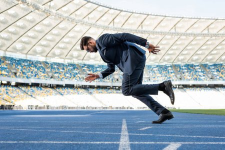 Photo pour Vue latérale d'un jeune homme d'affaires en costume de course au stade - image libre de droit