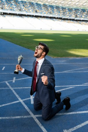Photo for Young businessman in suit standing on knees on running track with trophy and scream at stadium - Royalty Free Image