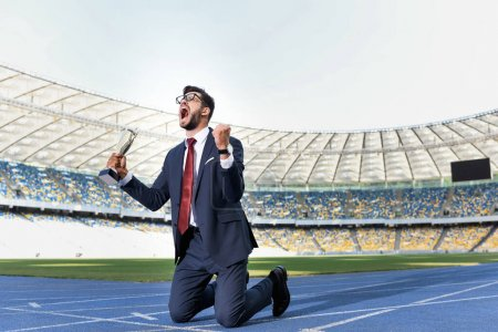young businessman in suit standing on knees on running track with trophy and scream at stadium