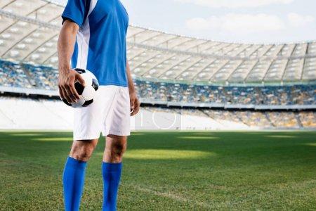 Photo pour Vue recadrée du footballeur professionnel en uniforme bleu et blanc avec ballon sur le terrain de football au stade - image libre de droit
