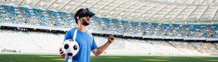 Photo pour Footballeur professionnel en casque vr avec des cris de balle et montrant un geste oui au stade, tir panoramique - image libre de droit