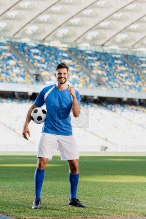 Photo pour Heureux footballeur professionnel en uniforme bleu et blanc avec ballon montrant oui geste sur le terrain de football au stade - image libre de droit