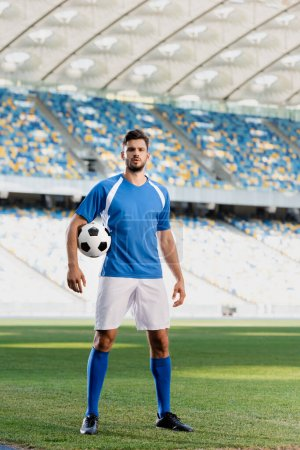 Photo for Professional soccer player in blue and white uniform with ball on football pitch at stadium - Royalty Free Image