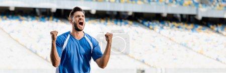 Photo pour Footballeur professionnel émotionnel en uniforme bleu et blanc montrant oui geste au stade, tir panoramique - image libre de droit