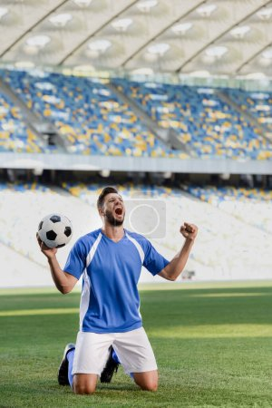 Photo pour Footballeur professionnel émotionnel en uniforme bleu et blanc avec ballon debout sur les genoux sur le terrain de football et montrant un geste oui au stade - image libre de droit