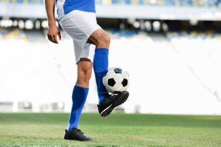 Photo pour Vue recadrée du joueur de football professionnel en uniforme bleu et blanc jouant avec le ballon sur le terrain de football au stade - image libre de droit