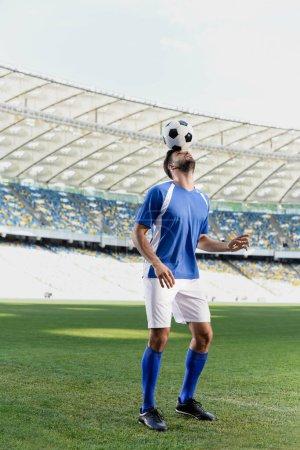 Photo pour Footballeur professionnel en uniforme bleu et blanc avec ballon sur la tête au stade - image libre de droit