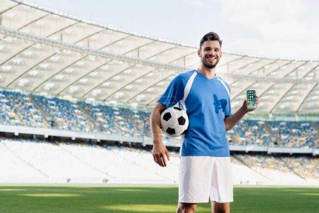 Photo pour KYIV, UKRAINE - 20 JUIN 2019 : joueur de football professionnel souriant en uniforme bleu et blanc avec balle montrant smartphone avec applications iphone au stade - image libre de droit