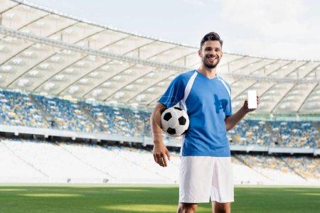 Photo pour Joueur de football professionnel souriant en uniforme bleu et blanc avec ballon montrant smartphone avec écran blanc au stade - image libre de droit