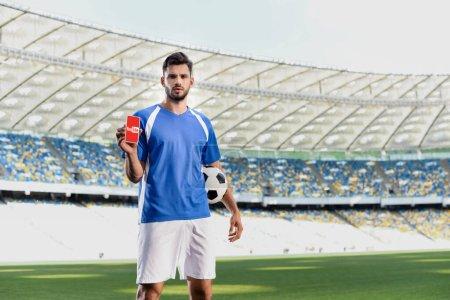 Photo pour KYIV, UKRAINE - 20 JUIN 2019 : footballeur professionnel en uniforme bleu et blanc avec ballon montrant smartphone avec application youtube au stade - image libre de droit