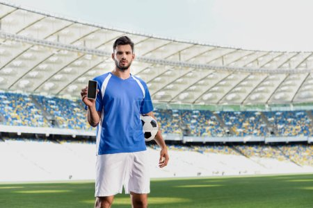 Photo for Professional soccer player in blue and white uniform with ball showing smartphone with blank screen at stadium - Royalty Free Image