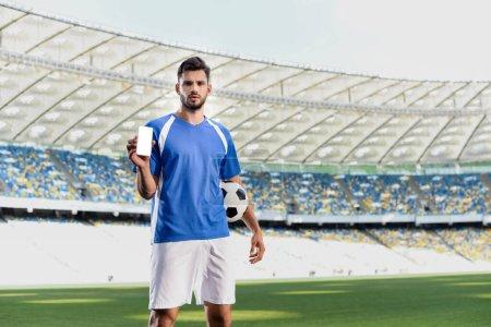 Photo pour Footballeur professionnel en uniforme bleu et blanc avec ballon montrant smartphone avec écran vierge au stade - image libre de droit
