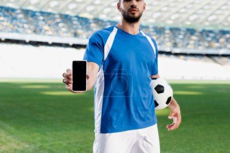 Photo pour Vue recadrée du joueur de football professionnel en uniforme bleu et blanc avec ballon montrant smartphone avec écran blanc au stade - image libre de droit