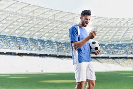Photo pour Footballeur professionnel émotionnel en uniforme bleu et blanc avec ballon en utilisant smartphone au stade - image libre de droit