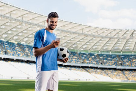 Photo for Smiling professional soccer player in blue and white uniform with ball using smartphone at stadium - Royalty Free Image
