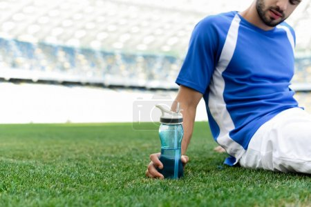 Photo for Cropped view of professional soccer player in blue and white uniform sitting on football pitch with sports bottle at stadium - Royalty Free Image